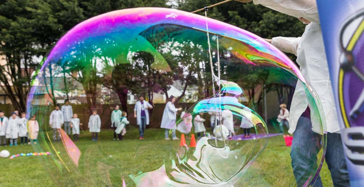 A kid in a mad science lab coat making a large bubble on grass