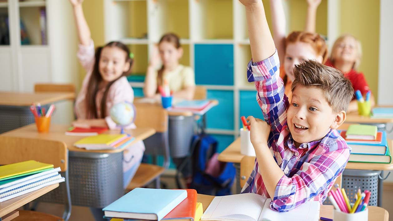 Boy in plaid shirt raising his hand in class with open notebook on his desk