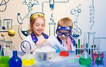 a boy and a girl wearing lab coats behind a desk with dry ice, beakers and tubes on it.